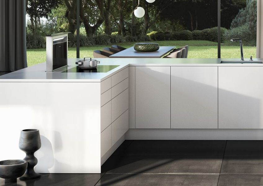 SieMatic Pure SE design woonkeuken onderkast in glanzende lotuswitte SQ-lak met downdraft-wasemkap.
