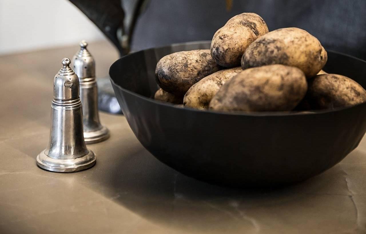 Salière et poivrière à côté d'un saladier de pommes de terre sur un plan de travail SieMatic.