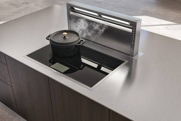 Extractor downdraft integrado en isla de cocina SieMatic Pure SE, con superficies de madera de roble y encimera de acero inoxidable.
