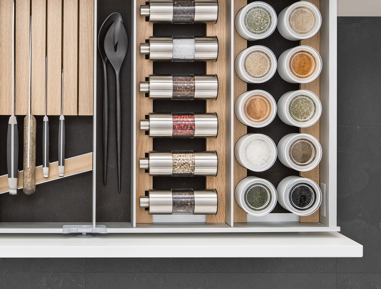 Het SieMatic Aluminium keuken lade-indeling systeem in licht eiken biedt plaats aan kruidenmolens, porseleinen potten en messen.