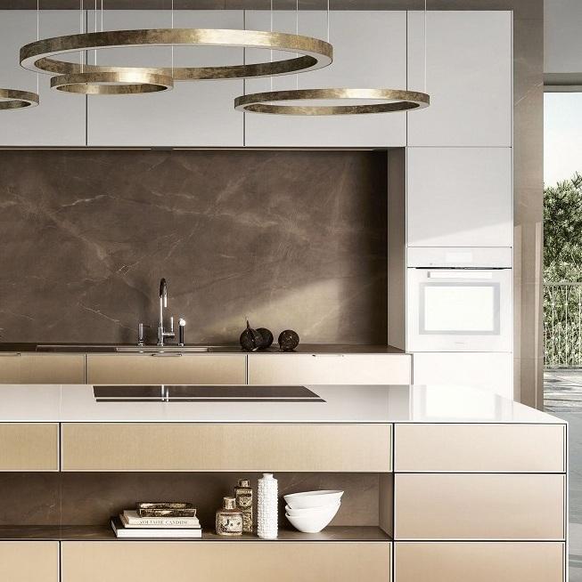 Vista de la SieMatic Pure SE 3003 R en blanco loto y bronce dorado, con isla de cocina.