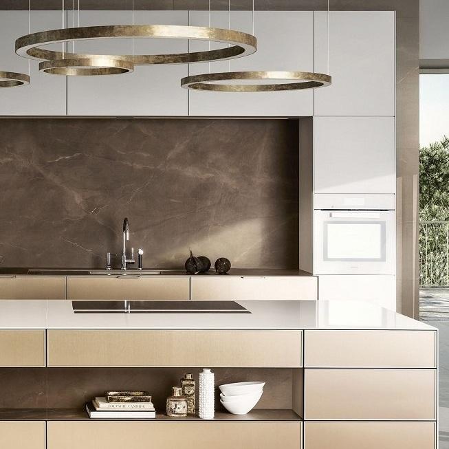 Blick auf die SieMatic Pure SE 3003 R in lotusweiß und goldbronce mit Kücheninsel.