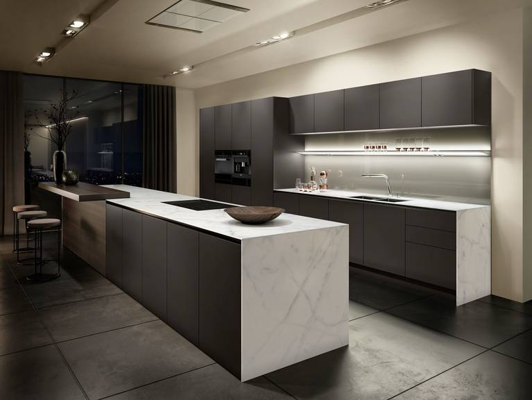 Handleless kitchen from the Pure style collection with SieMatic StoneDesign countertops and side panels in light-colored marble
