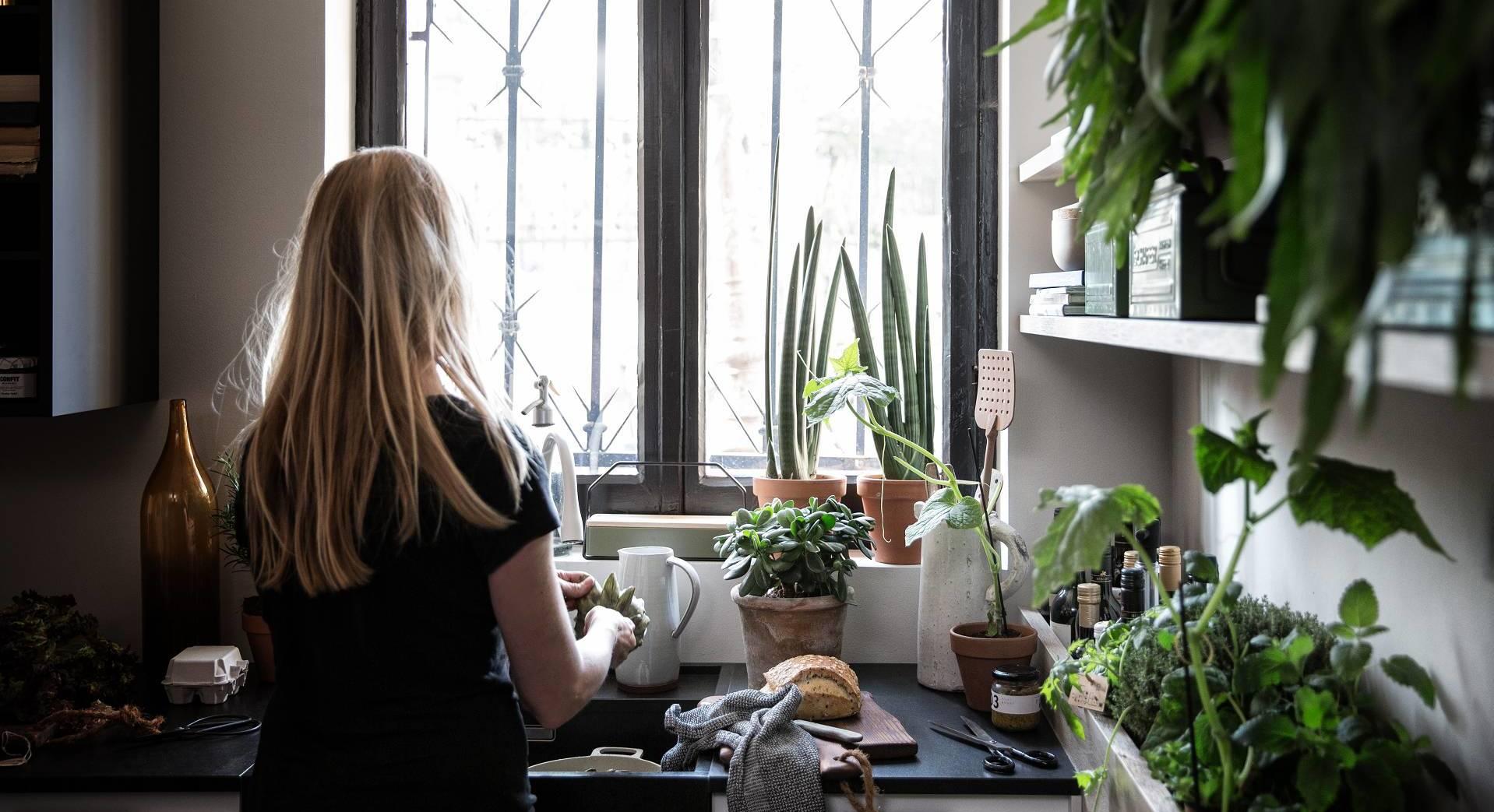 Frau beim Kochen in SieMatic Küche mit Kräutergarten.