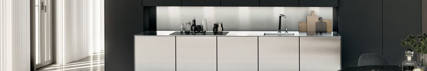 The niche behind this SieMatic stainless steel countertop offers storage space for spices, bottles and cutting boards.