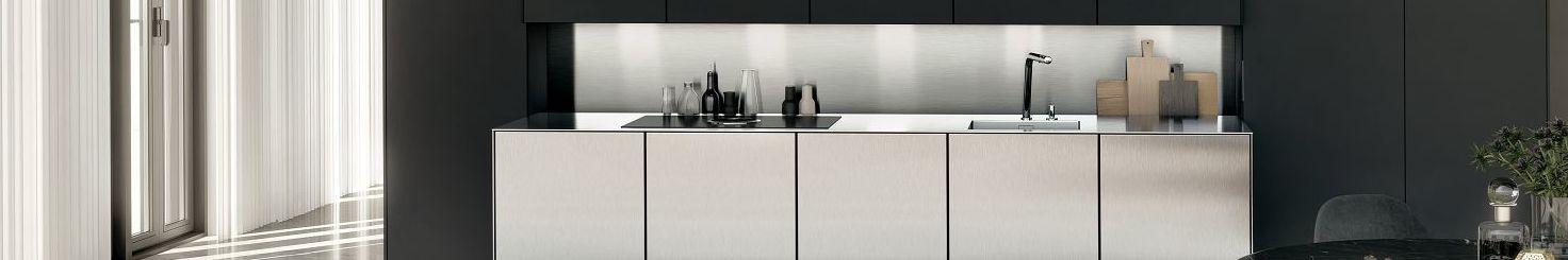 La niche derrière le plan de travail de cuisine haut de gamme SieMatic Pure en inox offre un espace de rangement pour les épices, bouteilles et planches à découper.