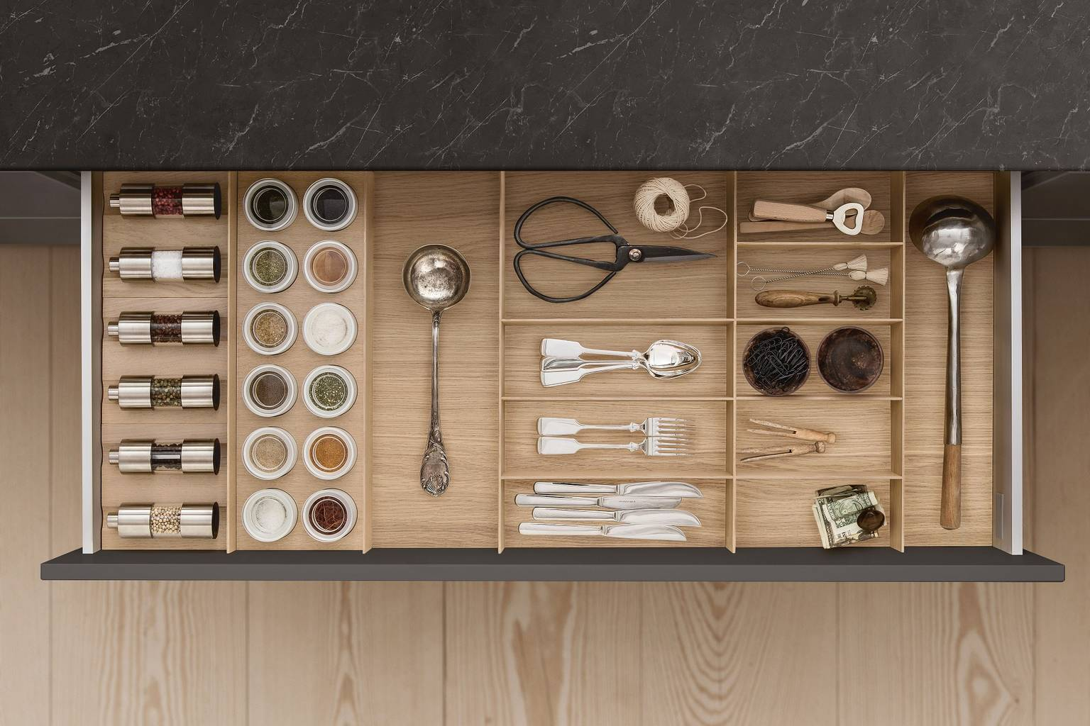 Cutlery, spice mills and porcelain jars in drawer with SieMatic kitchen interior accessories