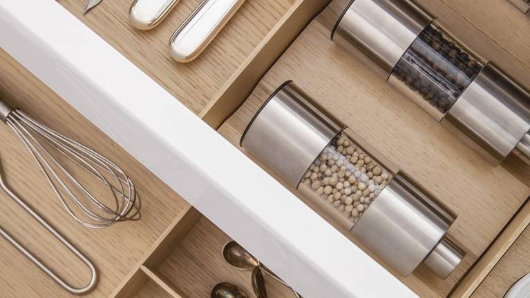 Macinini per spezie e vasetti in porcellana nel cassetto dell'attrezzatura in legno SieMatic.