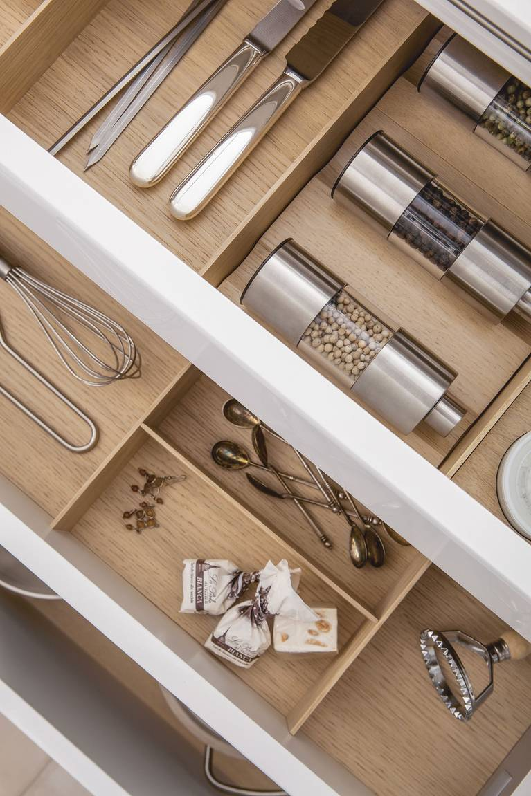 Spice mills and porcelain jars inside a SieMatic drawer with wooden accessories