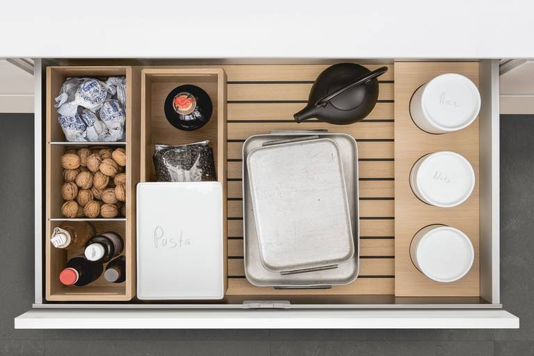 Porcelain containers, bottles and other supplies on SieMatic GripDeck with wooden kitchen accessories