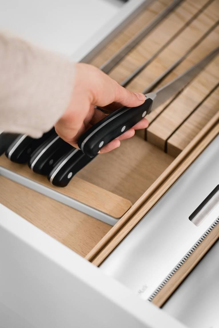 Soporte de cuchillos en roble claro para guardar cuchillos de calidad en un cajón de cocina SieMatic.